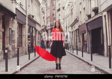 beautiful woman, portrait of girl with red umbrella standing on the street of Paris