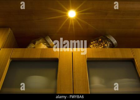 Detail of a wooden kitchen with star shape light and glass doors. - Stock Photo