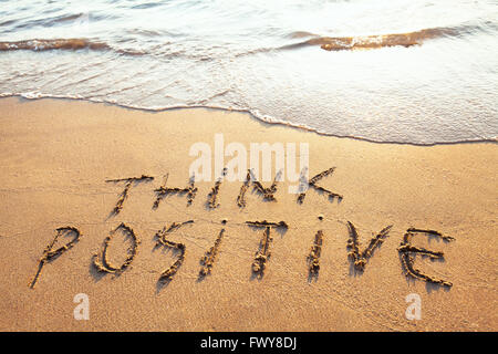 think positive, concept written on the sand - Stock Photo
