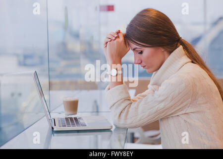 unemployment concept, problem, sad tired woman in front of laptop in modern bright cafe interior - Stock Photo
