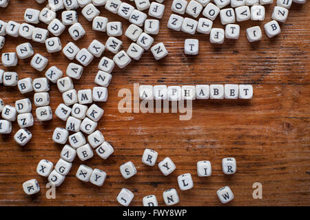 alphabet concept, word written with wooden letters, white english text on dark background, abc - Stock Photo
