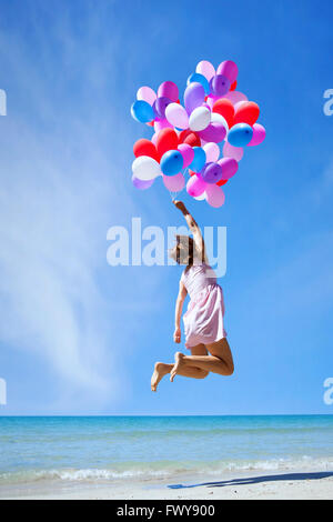 inspiration, happy people, woman flying with multicolored balloons in blue sky, creative concept - Stock Photo