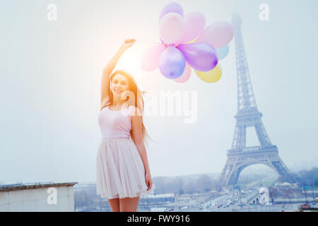 vacations in Paris, colorful dreams, happy girl with balloons near Eiffel tower - Stock Photo