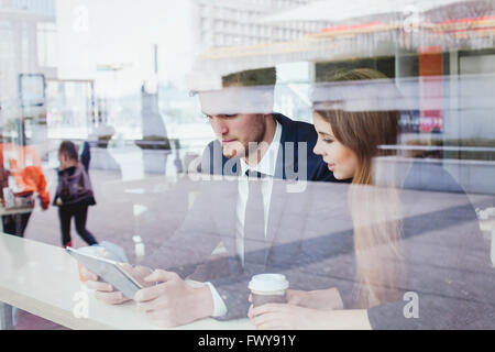 business people in cafe looking at the screen of tablet - Stock Photo