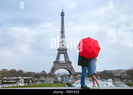 honeymoon in Paris, couple kissing behind red umbrella against Eiffel tower - Stock Photo