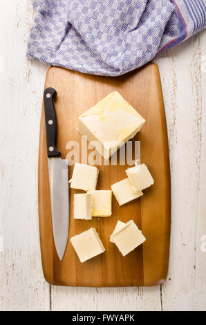 butter cubes and kitchen knife on a wooden board, kitchen towel in the background - Stock Photo