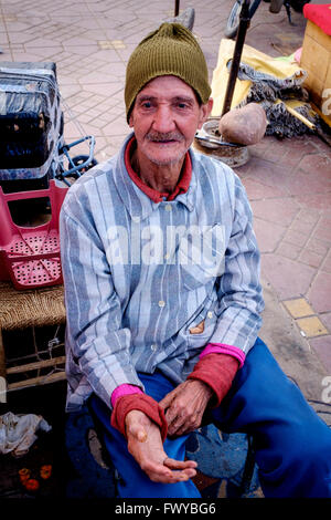 Portrait of a man who earns his living by shining shoes in the Jemaa el Fna, Marrakech, Morocco, North Africa - Stock Photo