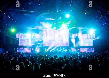 'Large crowd of festival goers at a popular music concert with their hands and phones up in the air. Thousand of - Stock Photo