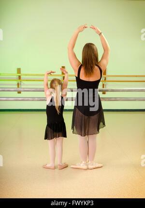 A Preschool Child with Teacher in Primary Ballet Class at Dance School Studio - Stock Photo