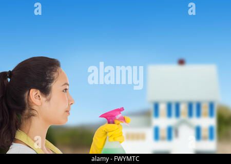 Composite image of woman spraying cleaning product - Stock Photo