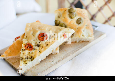 flatbread italy focaccia tomatoes olives flat oven baked Italian bread genovese ligure - Stock Photo