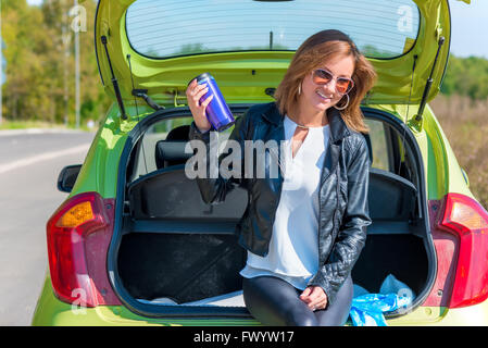 stylish beautiful girl on the sidelines of road resting - Stock Photo