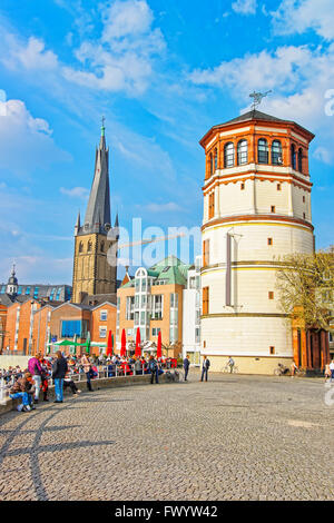 DUSSELDORF, GERMANY - MAY 3, 2013: St Lambertus Church and Schiffahrtmuseum in city center of Dusseldorf. Tourists nearby Stock Photo