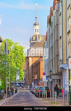 DUSSELDORF, GERMANY - MAY 3, 2013: Street view of the city center of Dusseldorf in Germany. Tower with spire and weathercock. Tourists nearby Stock Photo