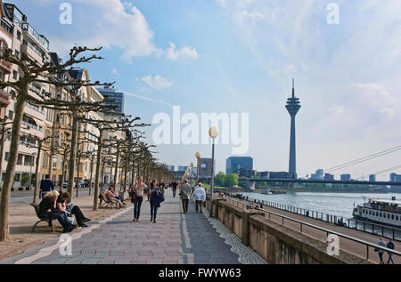 DUSSELDORF, GERMANY - MAY 3, 2013: Embankment with tourists, a tourist boat and Rheinturm Tower in Dusseldorf in Germany. The Harbor is also calles Medienhafen. Stock Photo