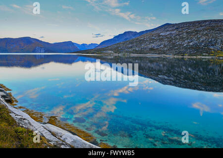 Stark mountains are reflected in the calm water of fjord Ejfjord on Ofoten in northern Norway. - Stock Photo