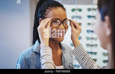 Attractive young African woman selecting glasses with the help of an optometrist in a store trying on different - Stock Photo