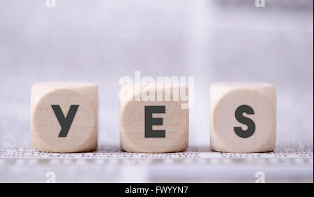 Yes word written on three wooden dice. - Stock Photo