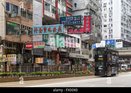Double-decker tram and buildings at the heavily built-up Causeway Bay in Hong Kong, China. - Stock Photo