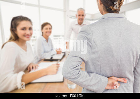 Composite image of businesswoman with fingers crossed behind her back over white background - Stock Photo
