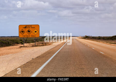 Empty remote long Eyre Highway road in Western Australia and warning sign about unfenced dangers from Kangaroo, - Stock Photo