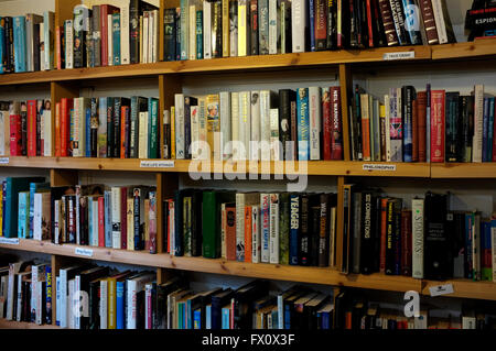 rows of secondhand fiction and non fiction books on wooden shelves in east kent uk april 2016 - Stock Photo