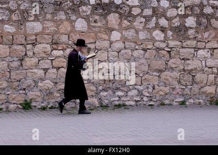 An Ultra orthodox Jew walking in the street on Shabbat at the German Colony or HaMoshava neighborhood in West Jerusalem - Stock Photo