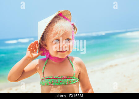 Portrait of beautiful little traveler on sunny white sand beach - happy smiling baby girl in vietnamese straw hat - Stock Photo