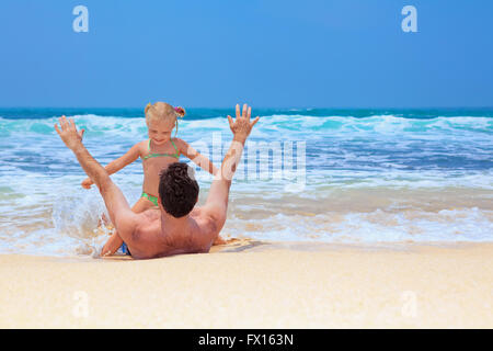 Father with daughter or grandfather with granddaughter play game with fun in sea surf on sea beach. - Stock Photo