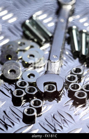Nuts bolts washers spanner steel background - Stock Photo