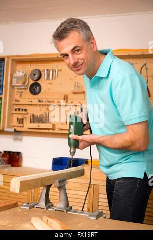 Do-it-yourselfer drilling in workshop - Stock Photo