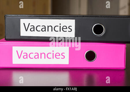 Bright office folders over dark background and vacancies text concept - Stock Photo