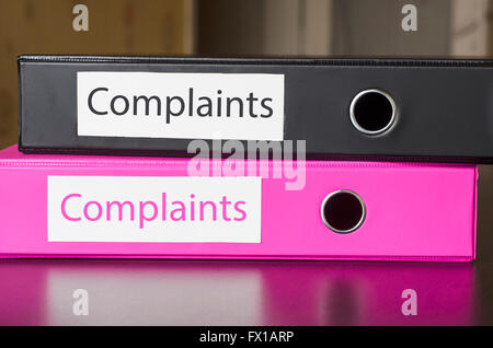 Bright office folders over dark background and complaints text concept - Stock Photo