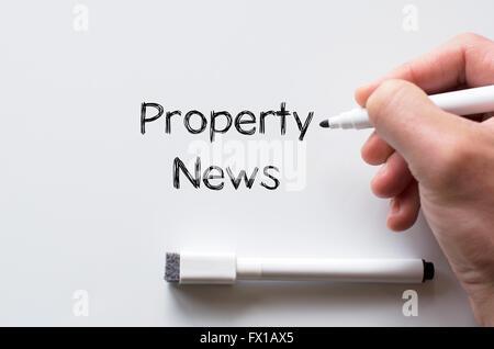 Human hand writing property news on whiteboard - Stock Photo