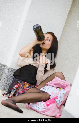Schoolgirl drinker single people sitting sit full length pour alcohol from bottle Pink bag Black nylon stockings - Stock Photo