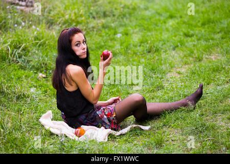 Teen girl eating apples on greenfield lifestyle girlnextdoor girl next-door outdoors attractive - Stock Photo