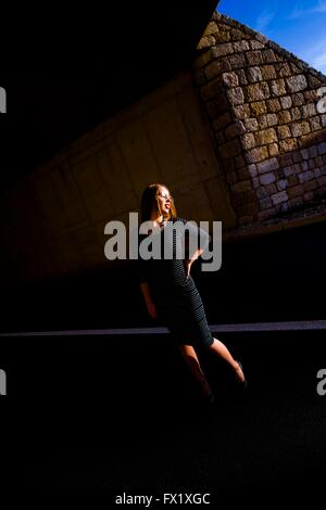 Young woman in darkness of road tunnel lighted by low sunset warm light outdoors attractive beautiful stand standing - Stock Photo