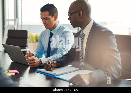 Two experienced business executives in a meeting seated at a table discussing paperwork and information on a laptop - Stock Photo