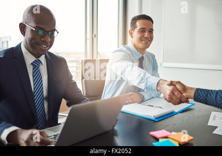 Smiling young Hispanic business man and woman shaking hands across a table in the office watched by a smiling African - Stock Photo