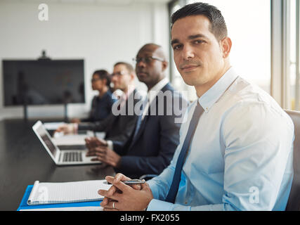 Young Hispanic businessman in a meeting with co-workers at the office sitting at a conference table turning to smile - Stock Photo