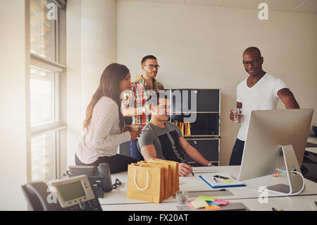Four young adults sitting around desk with computer, telephone, sticky notes and pen and paper next to bright office - Stock Photo