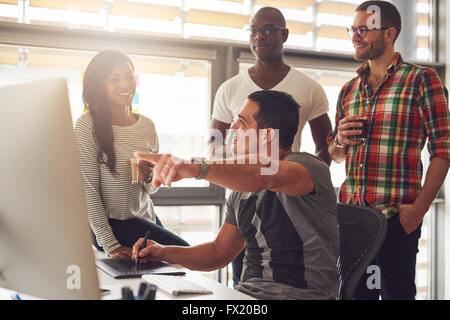 Man with stylus and tablet showing something on his computer to a group of three male and female casually dressed - Stock Photo
