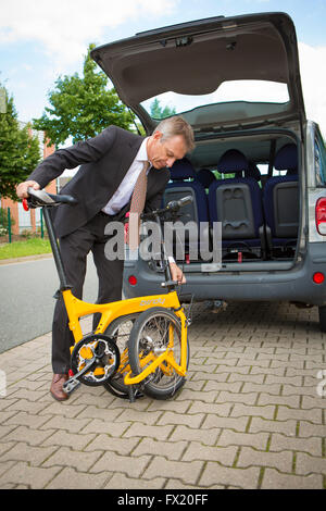 Business man grabs his folding bike in the car trunk - Stock Photo