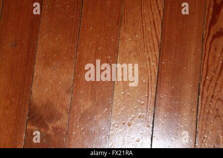 Knocked and battered varnished wooden floorboards - Stock Photo