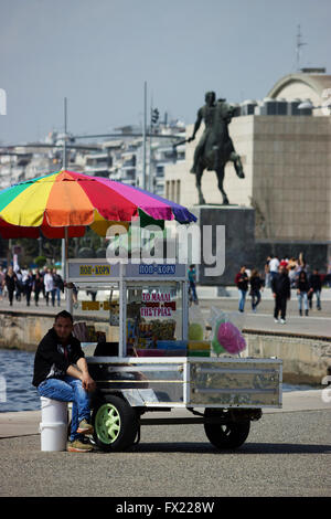 Street candyfloss seller with retractable concession cart in Thessaloniki's promenade. Alexander the Great statue - Stock Photo