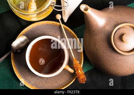A cup of hot tea on a table with teapot and honey. Shot from above - Stock Photo