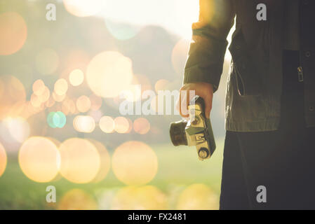 Female photographer shooting outdoors on autumn afternoon sunlight, retro toned image with selective focus - Stock Photo