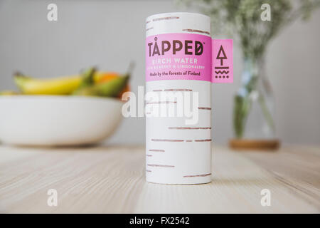 Tapped Birch water cartons on a wooden kitchen table in natural light. - Stock Photo