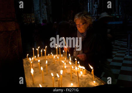 A woman lighting a candle in St Stephen's Cathedral Vienna - Stock Photo