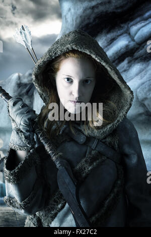 Wild girl archer in the snow with bow - Stock Photo